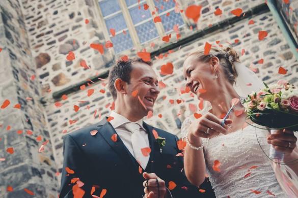 Hochzeitsfotografie in Schönebeck - Hochzeitsreportage mit glücklichem Brautpaar beim Auszug aus der Kirche im Blütenregen